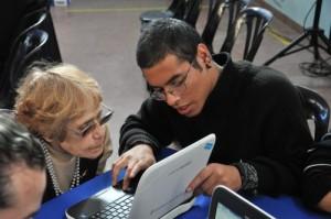 Usuario con discapacidad y persona mayor navegan en internet